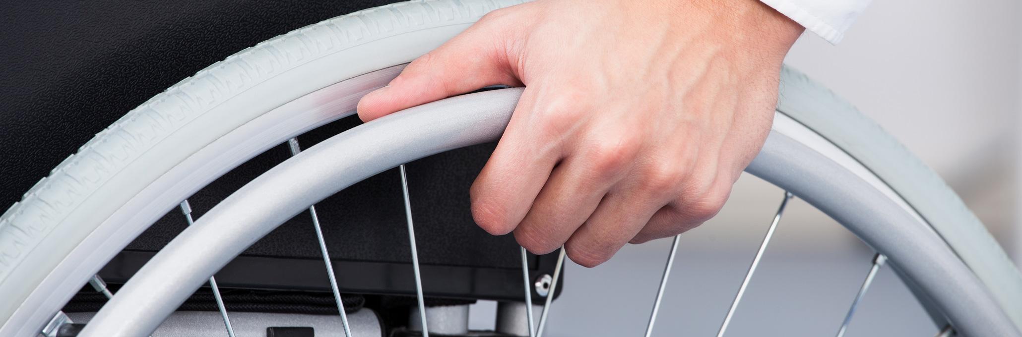 main sur une roue de fauteuil roulant